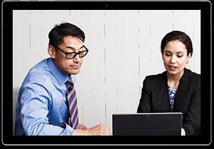 Foto von zwei Personen auf einem Tablet, die an einem Tisch sitzen und auf ein Surface im Laptopmodus schauen. Eine Person tippt auf dem Gerät.