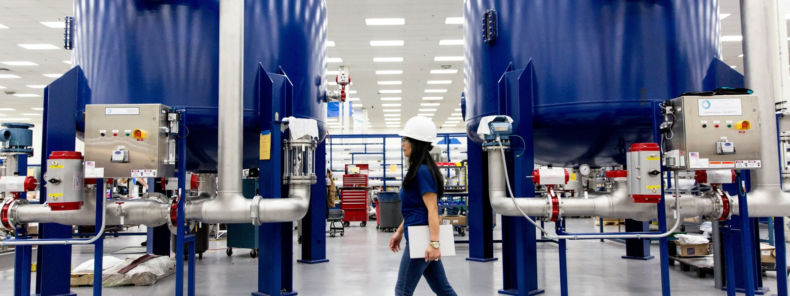 Woman in hard hat walking in manufacturing building