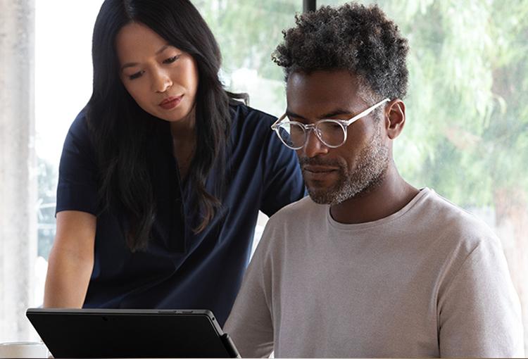 Foto von zwei Personen, eine stehend und die andere sitzend, die auf ein Surface im Laptopmodus schauen