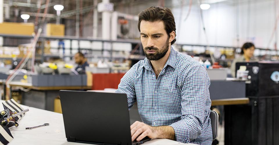 Foto einer Person, die an einem großen Tisch in einer Werkshalle sitzt und an einem Laptop arbeitet