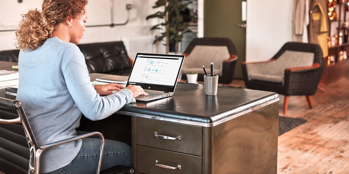 Women working at desk and using a laptop