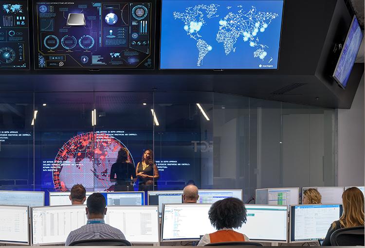 Foto von mehreren Personen, die im Microsoft Cyber Defense Operations Center an einem Tisch vor einer Reihe großer Monitore sitzen. Ein weiterer Monitor ist hoch oben an der Wand montiert.