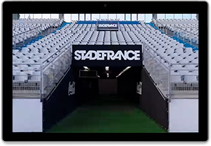 Still image from video framed inside a tablet. Image is entrance to stadium field tunnel underneath the grandstands with Stade de France painted in large graphic letters over the opening.