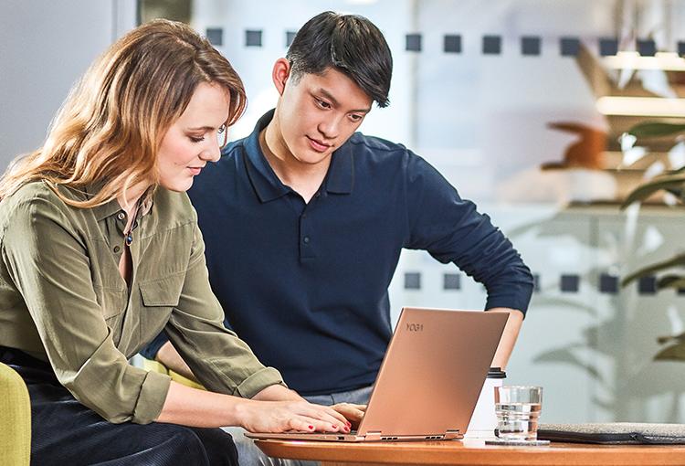 Foto von zwei Personen, die an einem Cafétisch sitzen und auf einen Laptop schauen. Eine Person tippt auf dem Gerät.