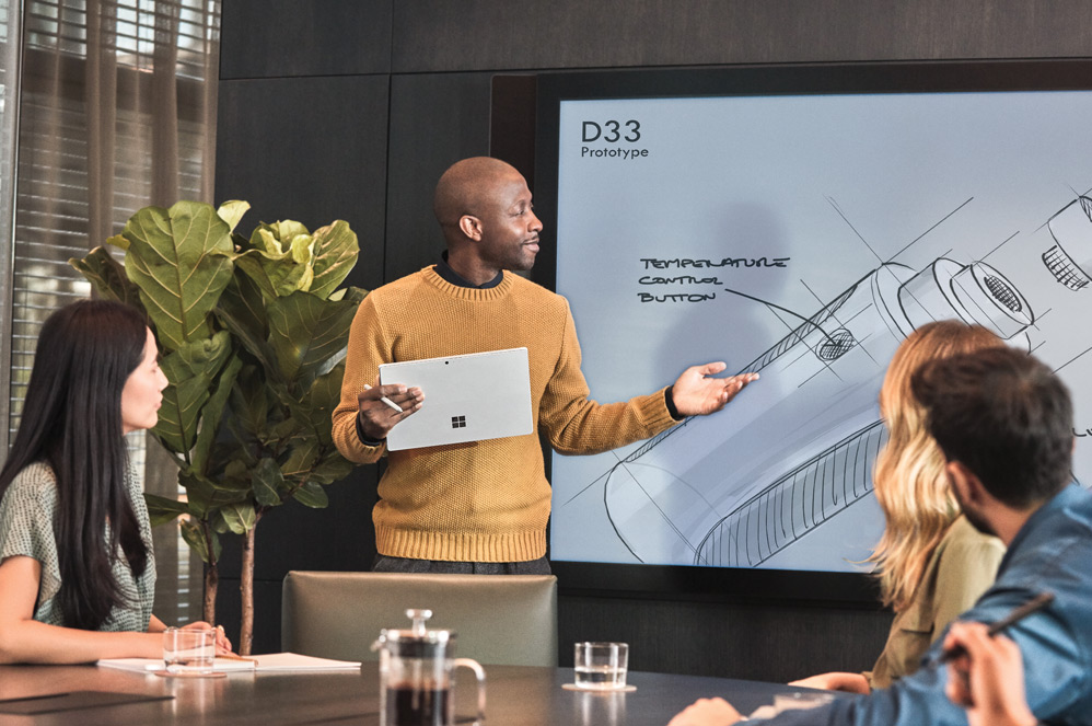 Business professional using Surface Pro 6 (Platinum) in tablet mode to present