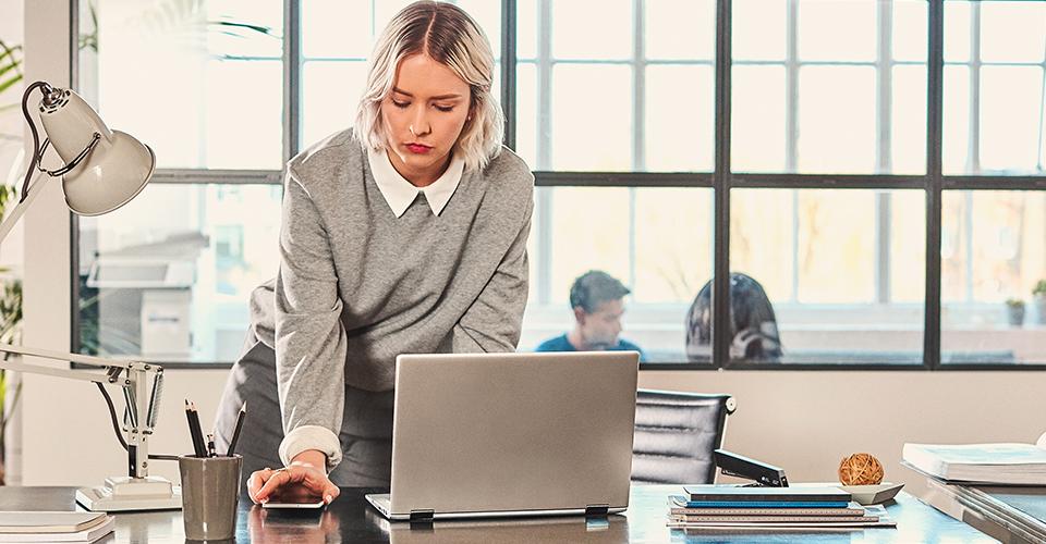 Une femme se tenant à un bureau et se connectant à son ordinateur portable.