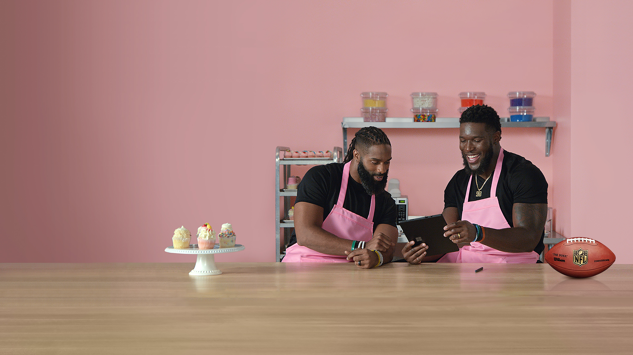 Two football players wearing aprons stand in kitchen looking at a Surface Pro. There are a plate of cupcakes and a football in the foreground.