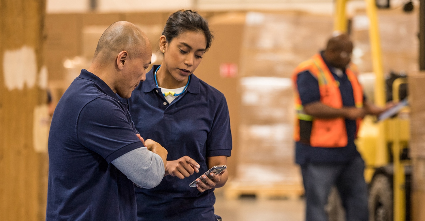 Two workers talking while looking at a mobile phone.