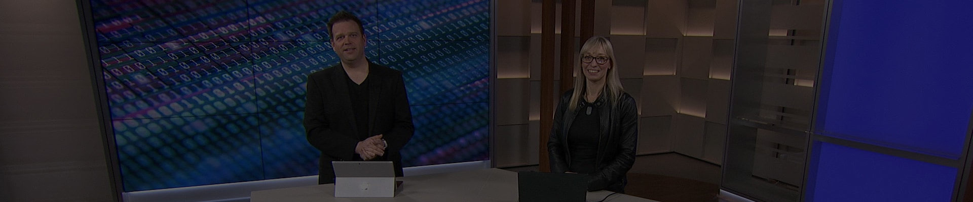 Still image from webcast video with two people in a studio at a counter with a laptop and a Surface Pro