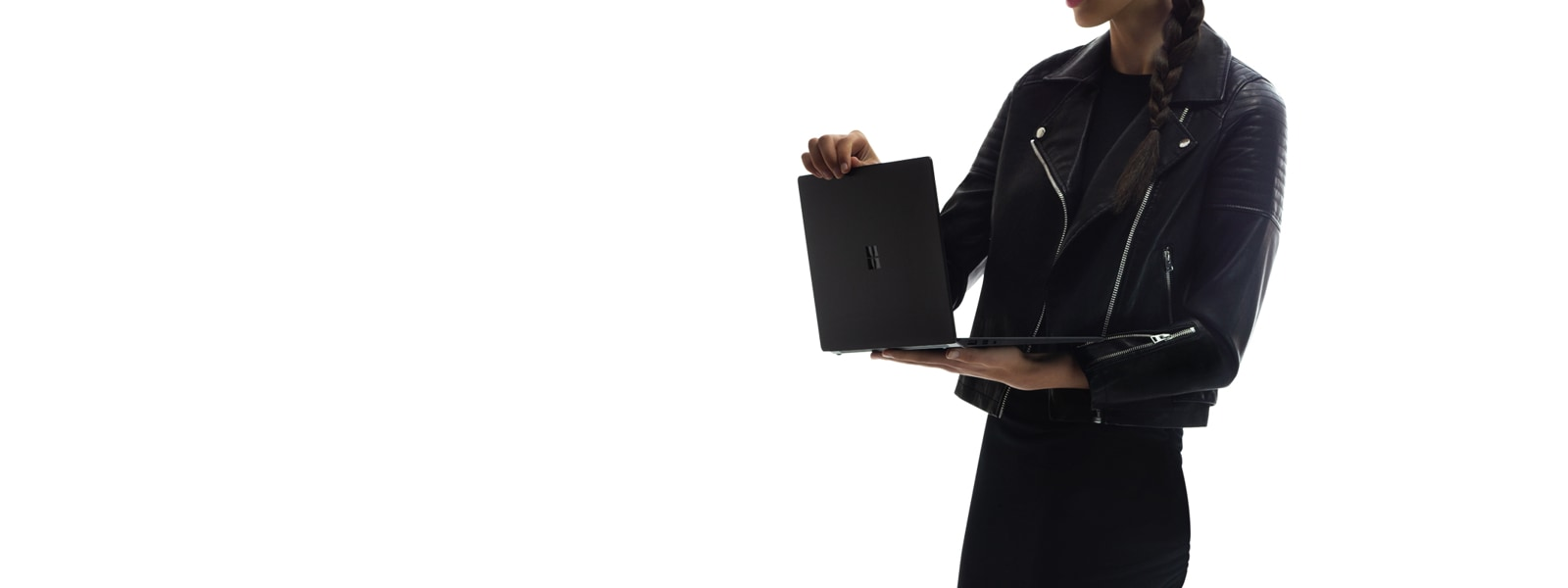 A woman holding Surface Laptop 2 computer