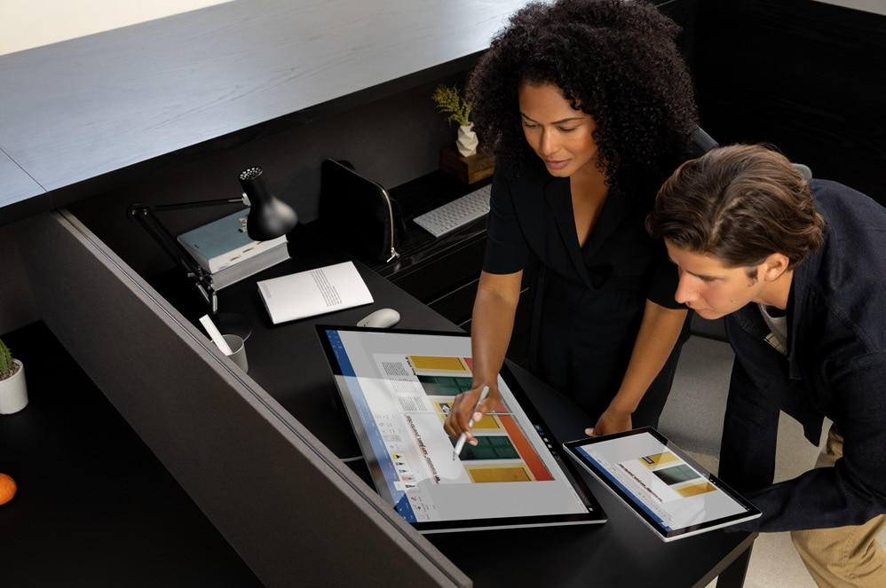 Two people interacting with the Surface Studio 2 computer