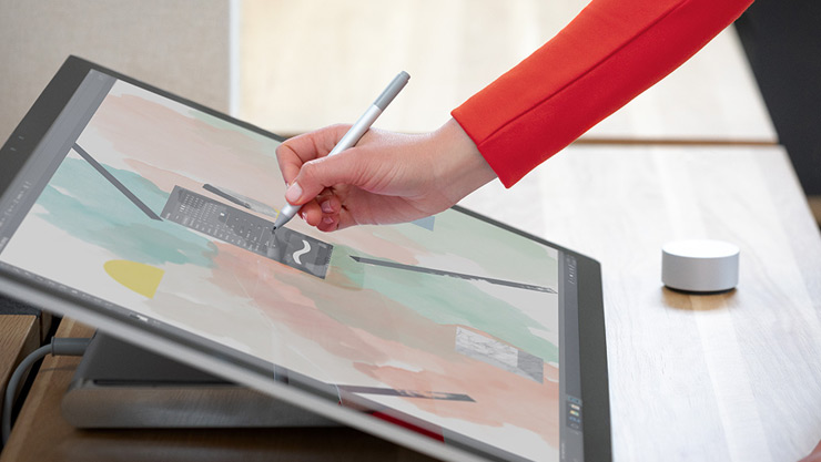 有個人與 Surface Studio 2 和螢幕上的 Surface Dial 互動