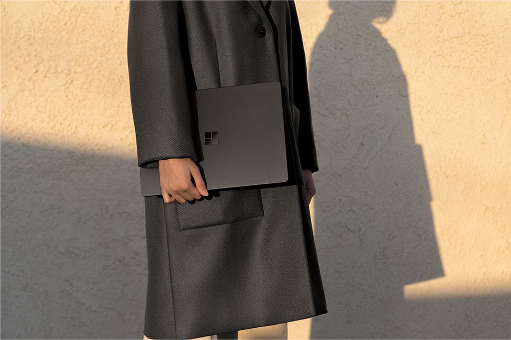有個人拿著黑色 Surface Laptop 2
