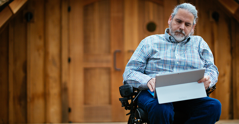 Photograph of a person with a disability sitting in a wheelchair outside while working on a Surface in laptop mode