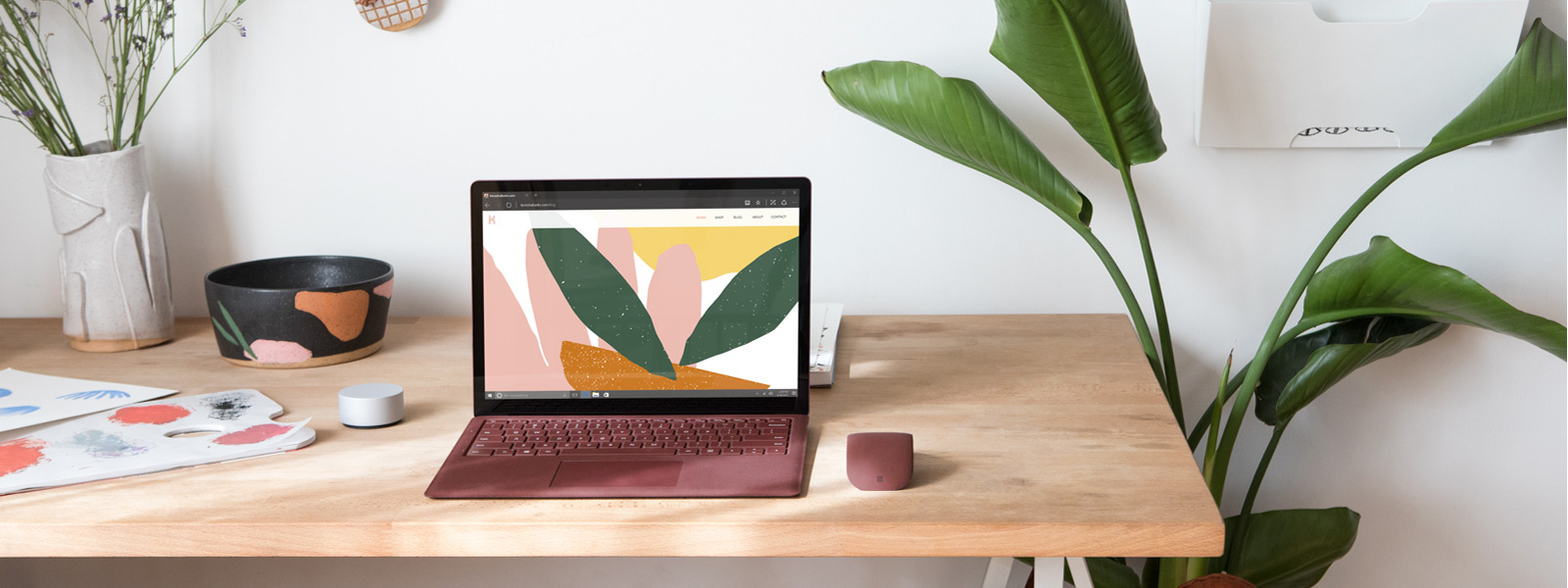 Lifestyle shot of Microsoft Surface Laptop (burgundy) in office