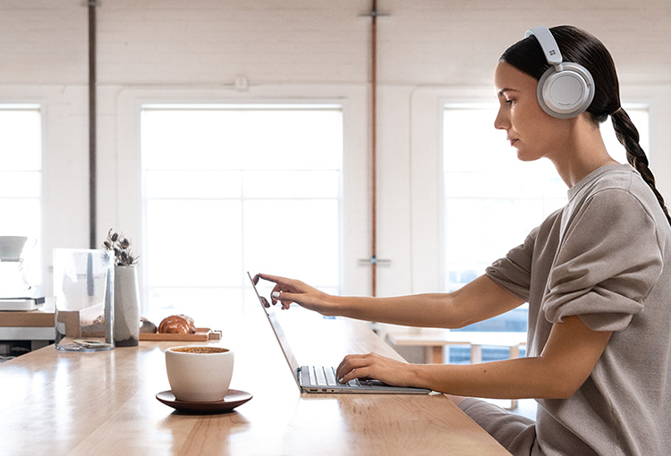 Photograph of person wearing headphones seated at a counter touching the screen of a laptop