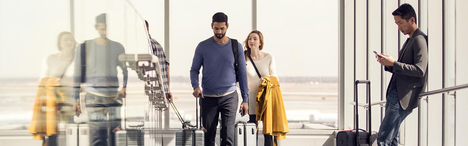 Photo d'un aéroport avec des voyageurs marchant avec des bagages. Un voyageur est debout près de ses bagages et consulte son téléphone portable.