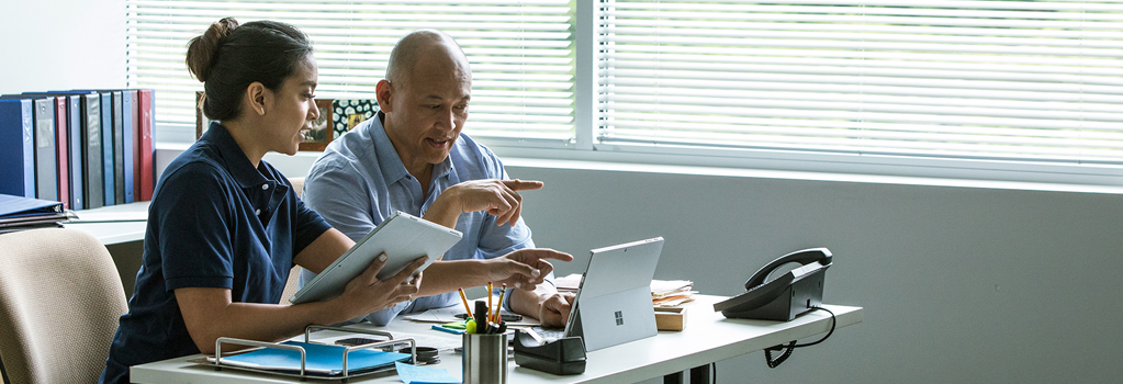 Photograph of two people in an office sitting at a desk talking while pointing at a Surface in Laptop mode, one is holding a Surface in Tablet mode