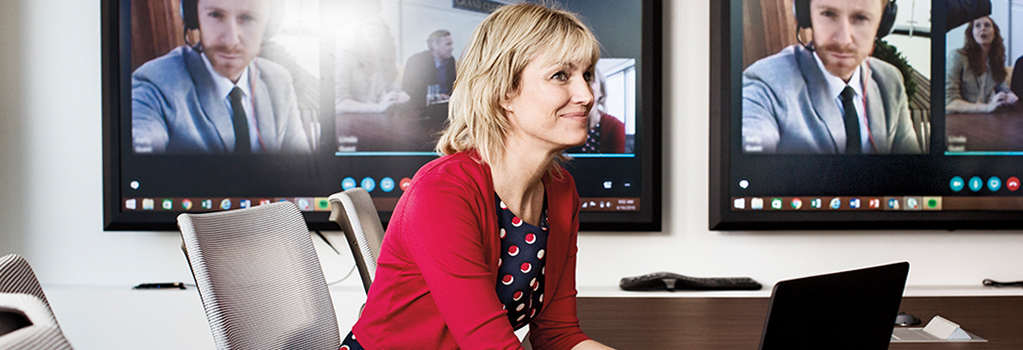 Photograph of a person seated at a table in a large conference room taking part in a video conference with participants displayed on large wall-mounted monitors