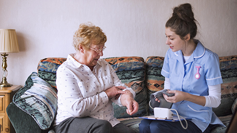 Young woman applying blood pressure cuff to older woman.
