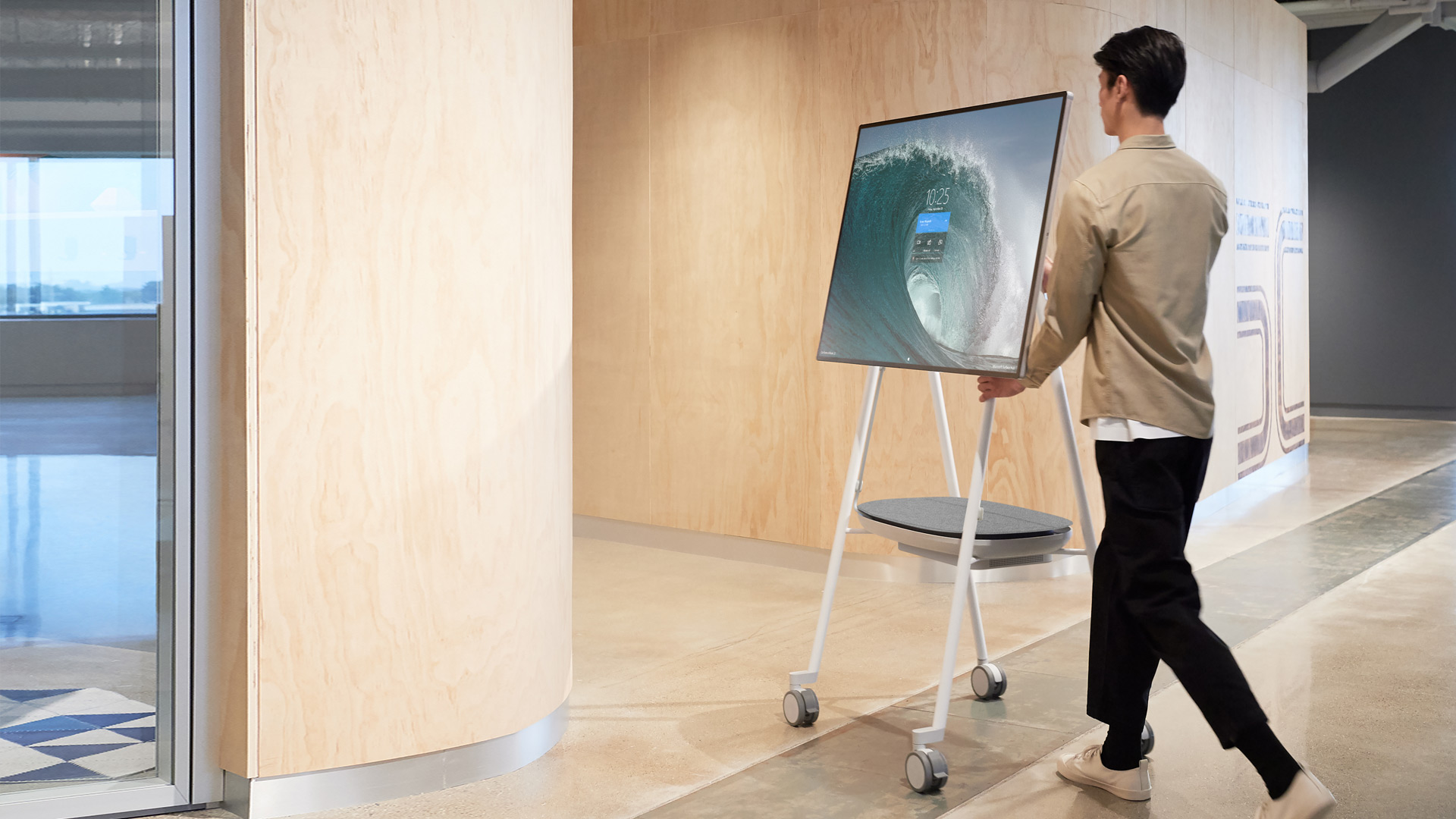 With the display still on, a man moves Surface Hub 2S on a  Steelcase Roam™ rolling mobile stand with the APC™ Charge Mobile Battery
