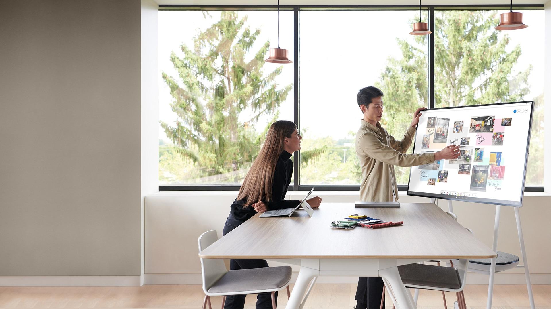 オープンオフィス環境で 2 人のチームメンバーが Surface Hub 2S を使用してアイデアをホワイトボードに書いている様子