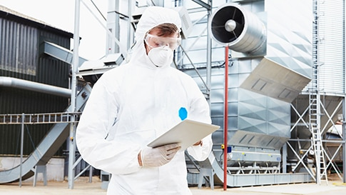 Workers in protective suits using a tablet