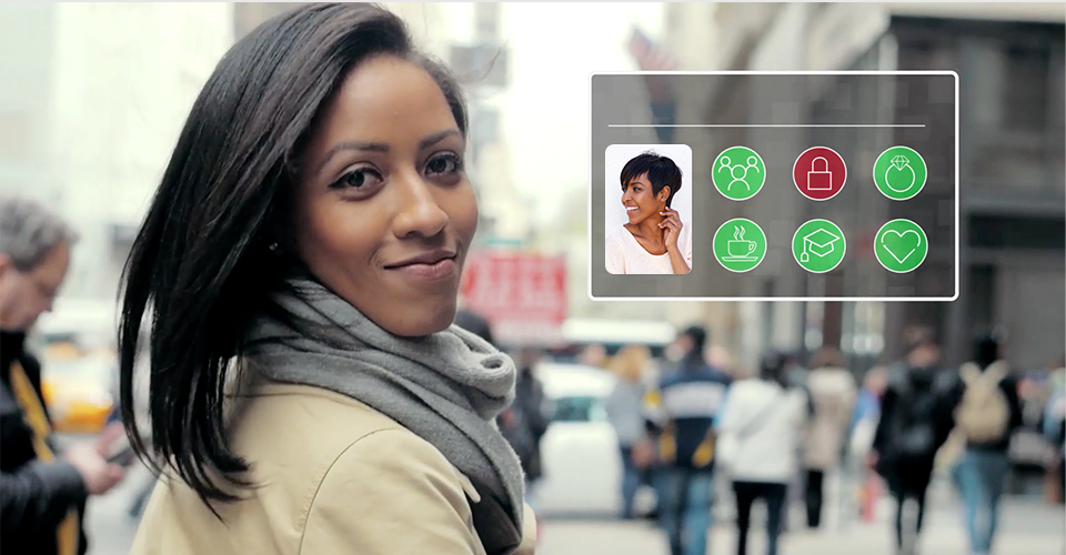 Still image from video of a person standing on a busy city sidewalk next to a representation of their owned identity. The identity includes a photograph and icons representing various activities and items including a padlock.