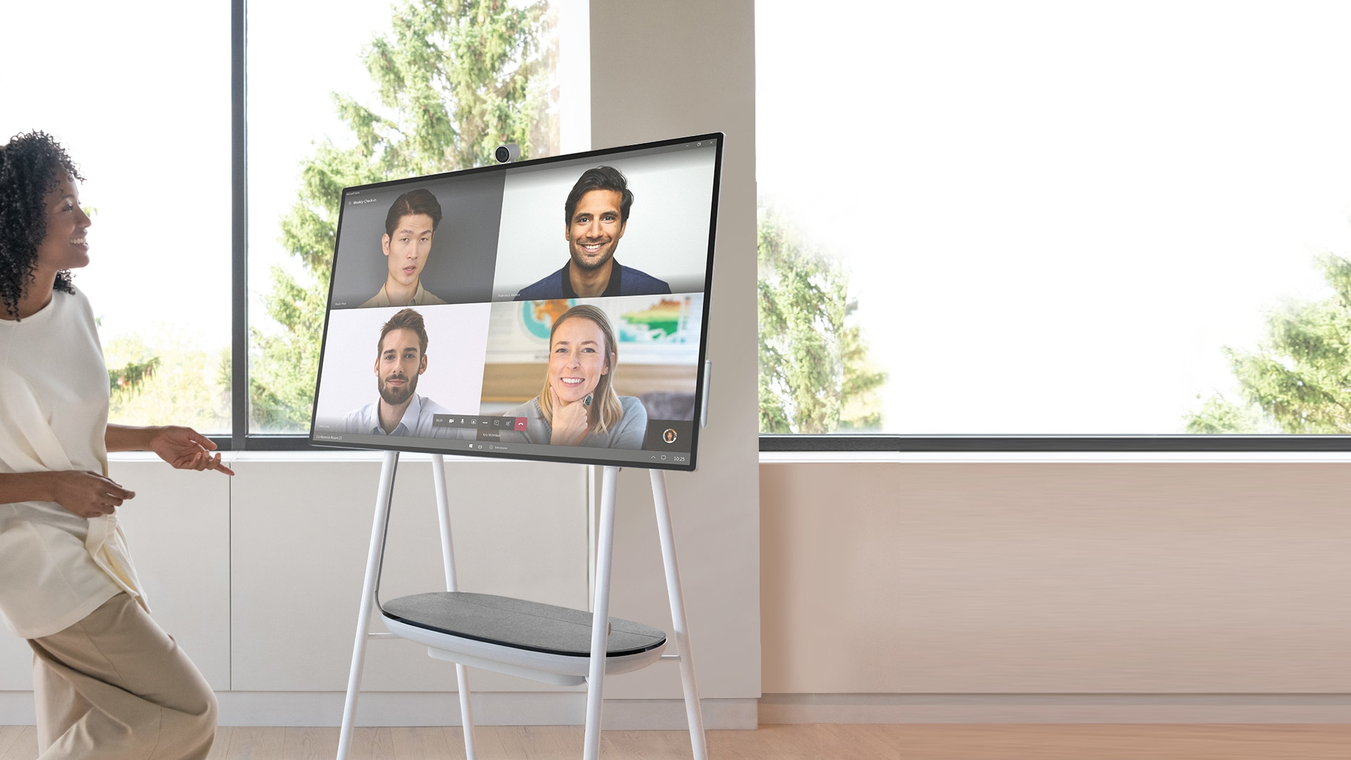 A woman casually stands near a Surface Hub 2S in a video conference with four remote team members