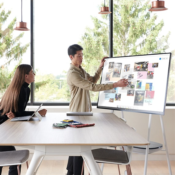 Photograph of people collaborating in front of a Surface Hub electronic whiteboard.
