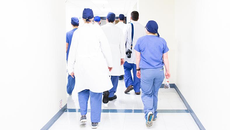 group of medical professionals walking down hospital corridor
