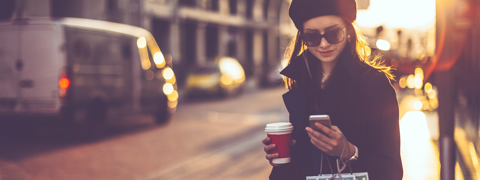 Woman holding shopping bag and coffee cup while looking at her phone