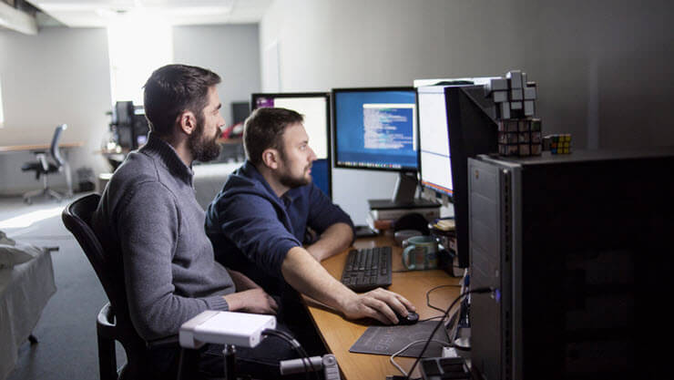 Two software developers sitting using a computer.