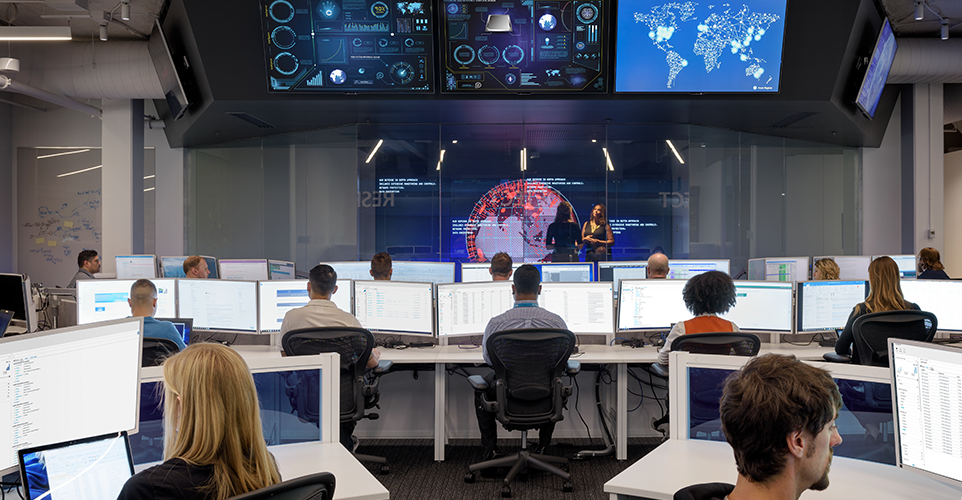 Photograph of people working at desks with large monitors in the Microsoft Cyber Defense Operations Center. In an adjacent room with glass walls, two people are talking in front of a giant monitor.