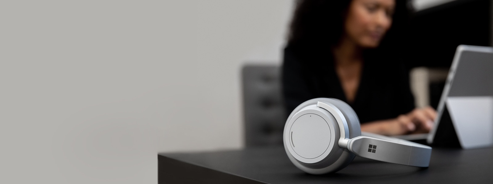 Surface Headphones rest on a desk in front of a woman using a Surface Pro in the background