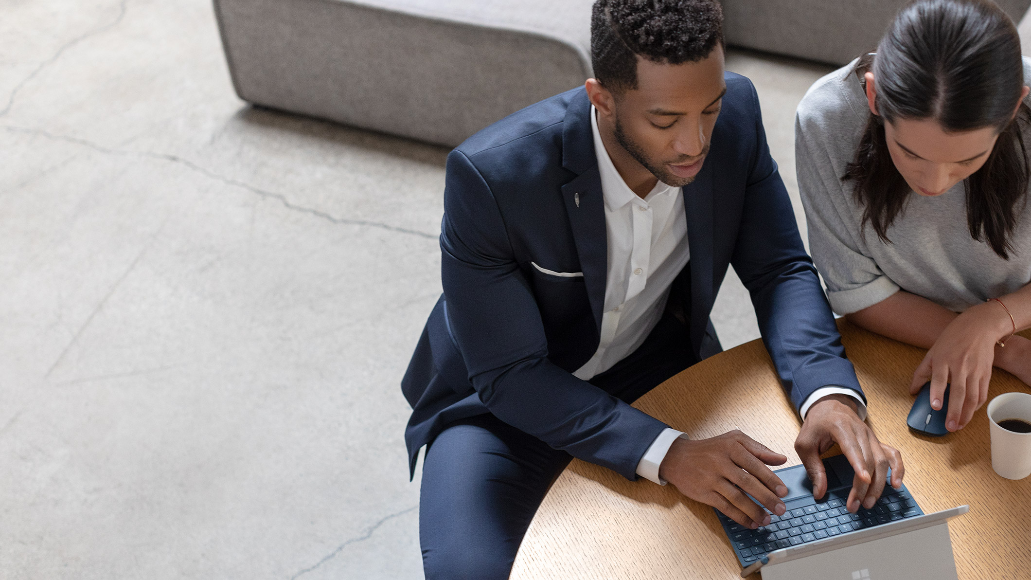 business professionals sitting at a conference table viewing information on a laptop
