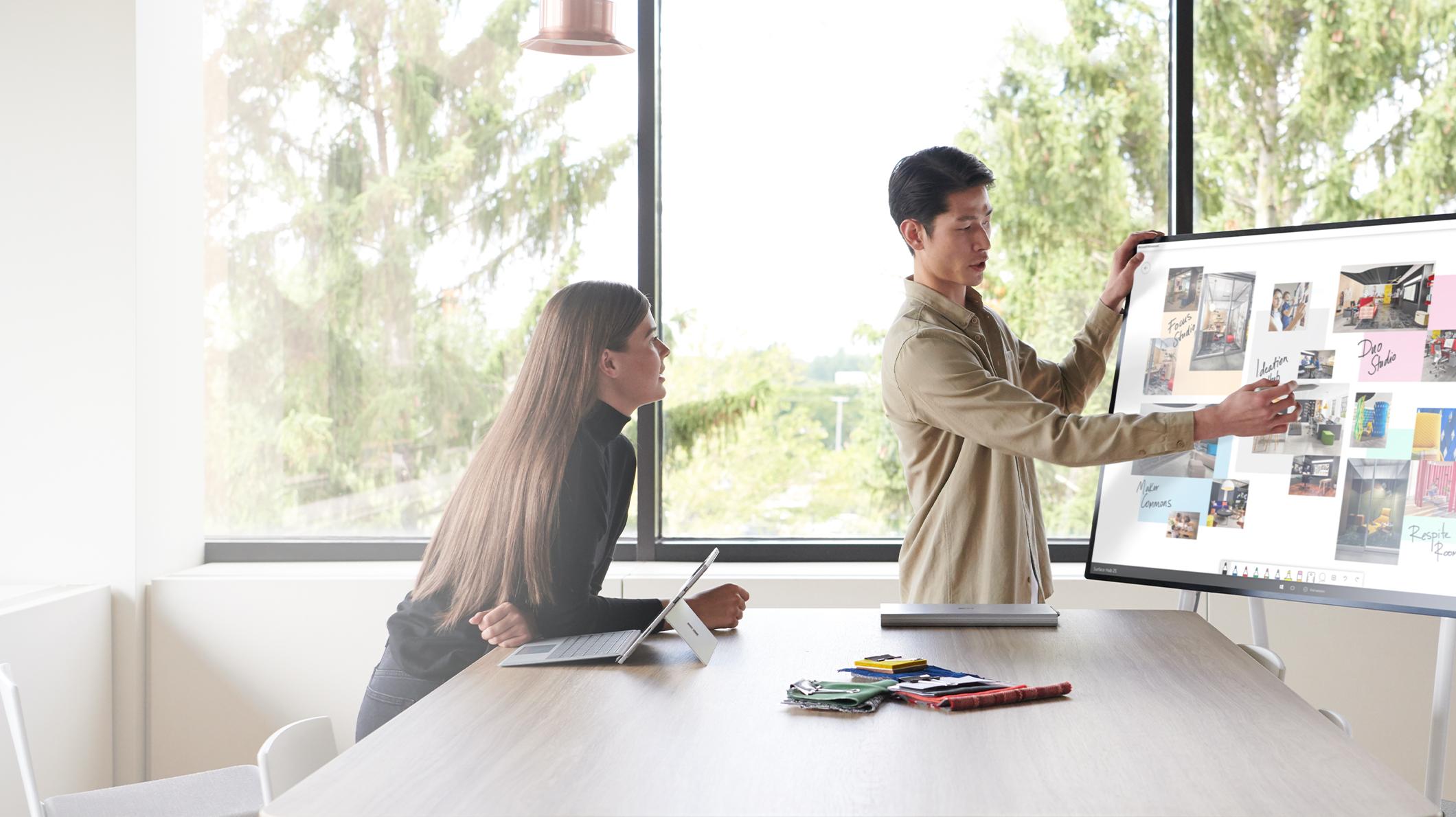 رجل يشير إلى جهاز Surface Hub 2S ويتعاون مع امرأة