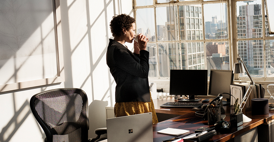 Photograph of person in an office standing behind a large desk looking out window. On the desk are multiple monitors and a Surface Book along with multiple other traditional office tools and supplies.