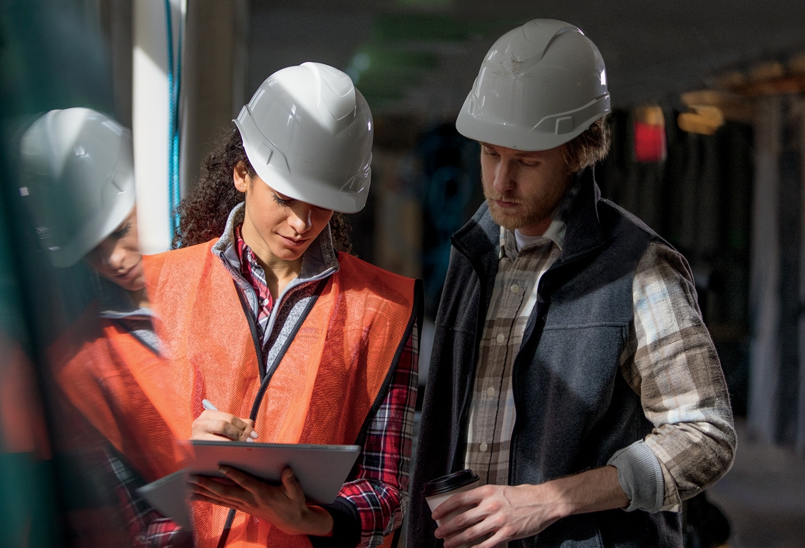 Photograph of two people wearing construction hard hats and gear talking inside a building that is under the final stages of construction. One of them is holding a tablet device.