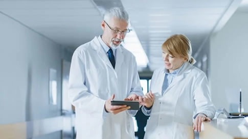 Man and woman dr. in white coats looking at tablet