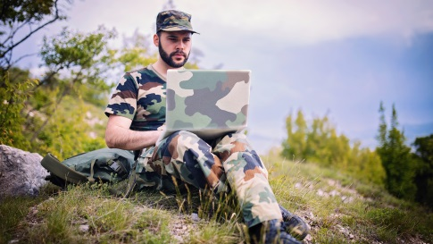 Outdoor setting of a man in camouflage military uniform sitting on the ground working on a laptop computer with camouflage cover.