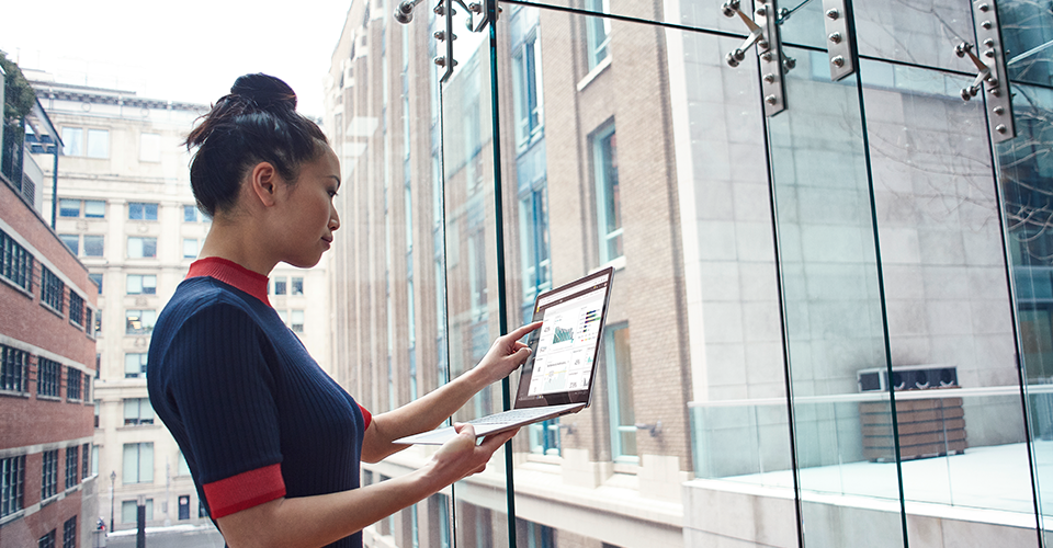 Photograph of a person standing in an enclosed walkway between two office buildings looking at information displayed on a laptop