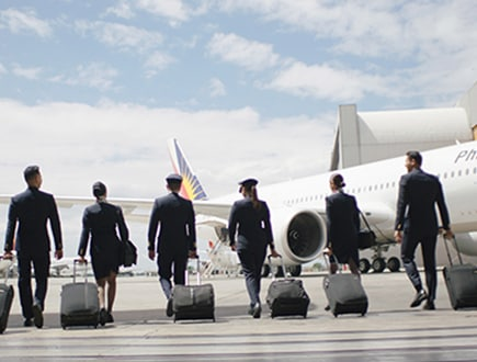 Image of flight crew walking toward a plane on the tarmac