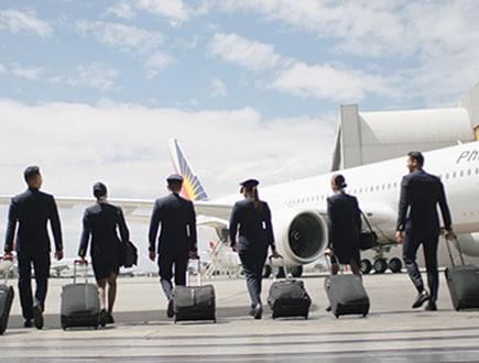 Image of flight crew walking toward a plane on the tarmac