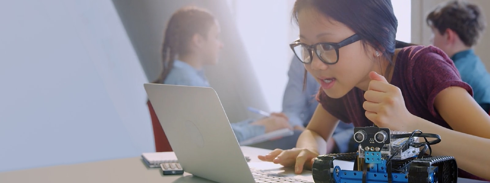 Girl works on a computer next to a robot in a classroom.