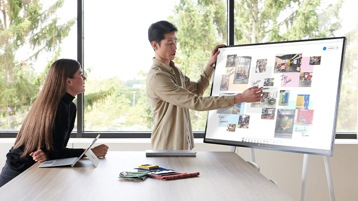 Hombre que apunta al Surface Hub 2S mientras colabora con una mujer