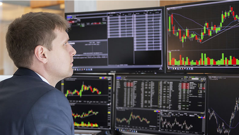 man sitting at desk viewing data charts on multiple monitors
