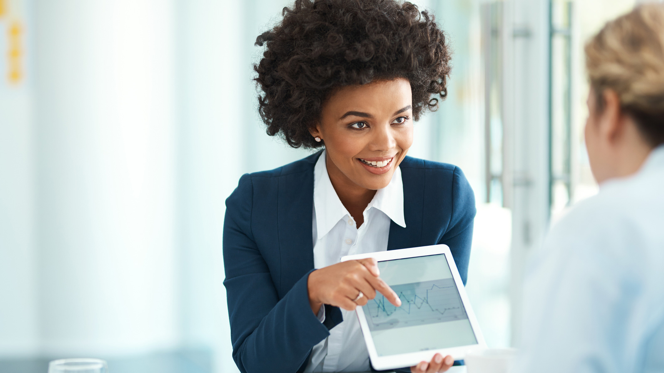 female insurance professional showing client data on a tablet