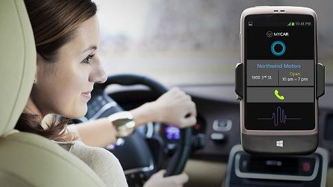 Eine Frau sitzt in einem Auto am Steuer, neben ihr ein neues Device