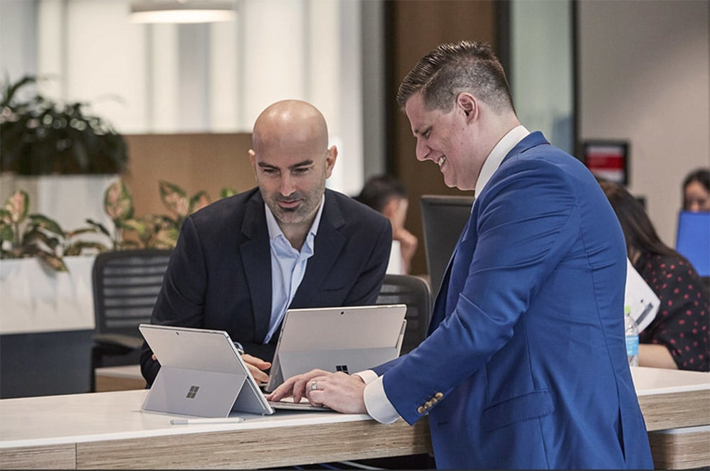 Two male office workers collaborating on a Surface device